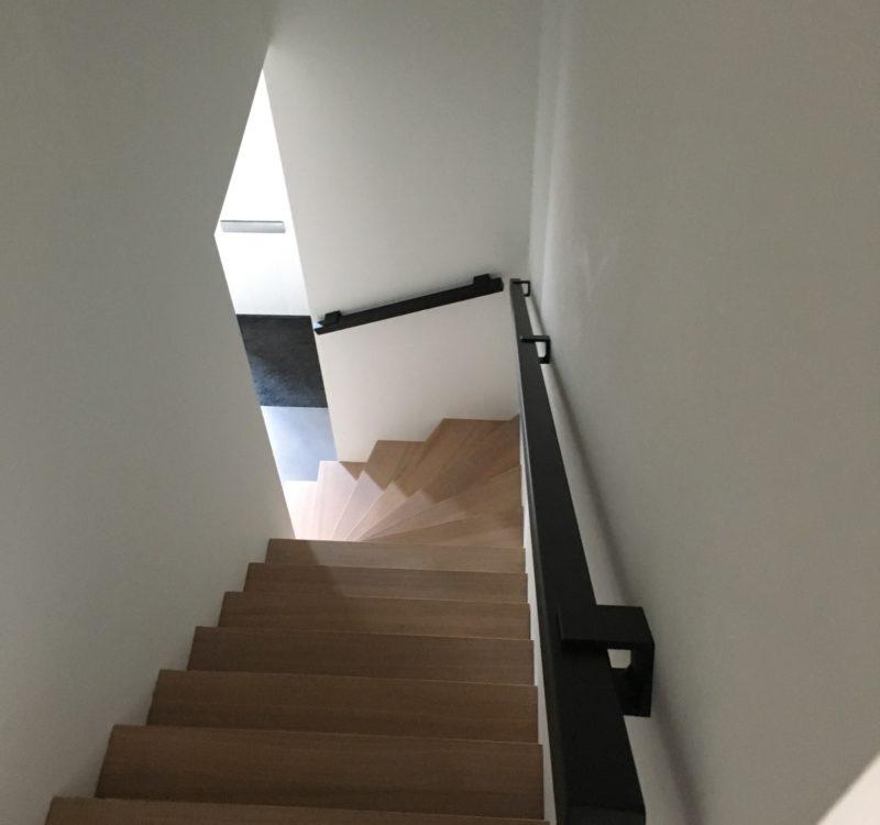 Vierkante stalen trapleuning matzwart langs houten trap