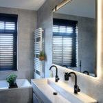 Badkamerspiegel met stalen omlijsting aan roede met ledverlichting