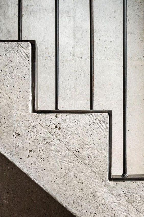 Betonnen trap met zwarte stalen balustrade langs treden