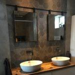 Twee spiegels met zwart frame aan een roede