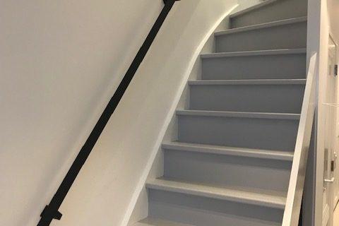 Platte stalen trapleuning met leuninghouders aan onderzijde