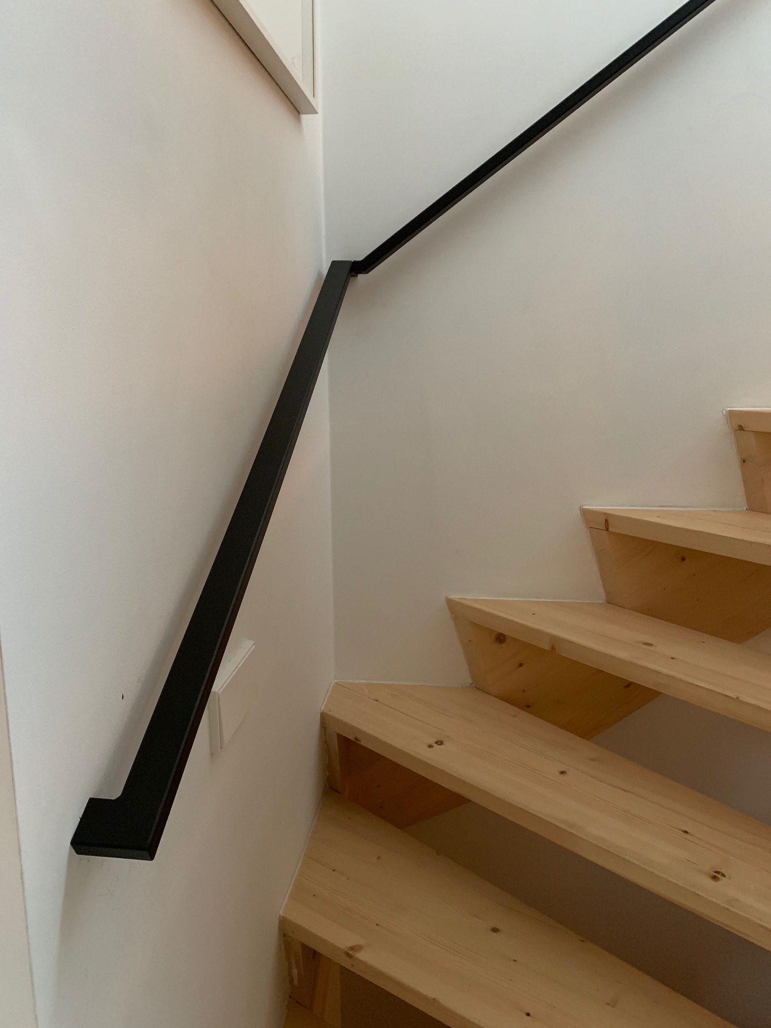 Doorlopende stalen trapleuning, matzwart gepoedercoat bij een houten trap